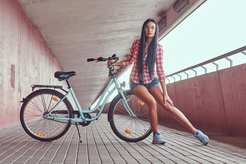 Beauty brunette female wearing a pink flannel shirt and denim shorts in glasses, sitting by a wheel on a city bike, in a stock photos