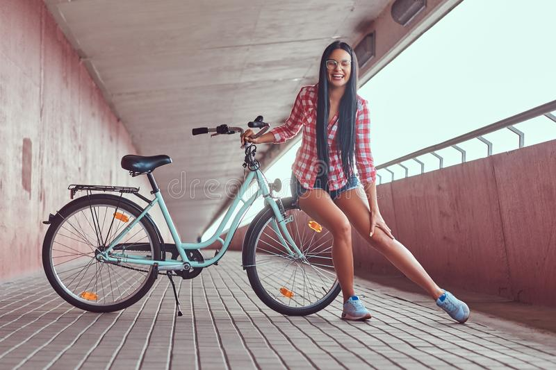 Beauty brunette female wearing a pink flannel shirt and denim shorts in glasses, sitting by a wheel on a city bike, in a royalty free stock photography