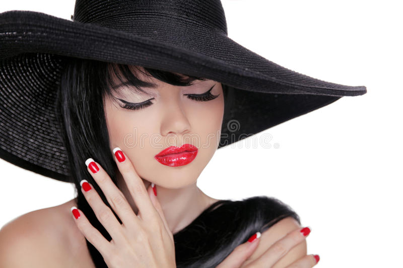 Beauty Brunette Woman with glamour bright makeup and red manicure nails wearing in black hat isolated on white background stock image