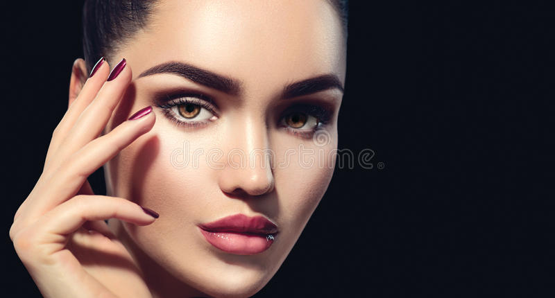 Beauty brunette woman with perfect makeup isolated on black stock photos