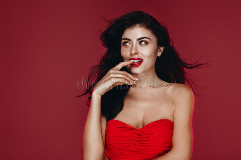 Beauty Brunette Woman with Perfect Makeup in red dress. Beautiful Professional Holiday Make up. Beauty Girl Face studio stock photography