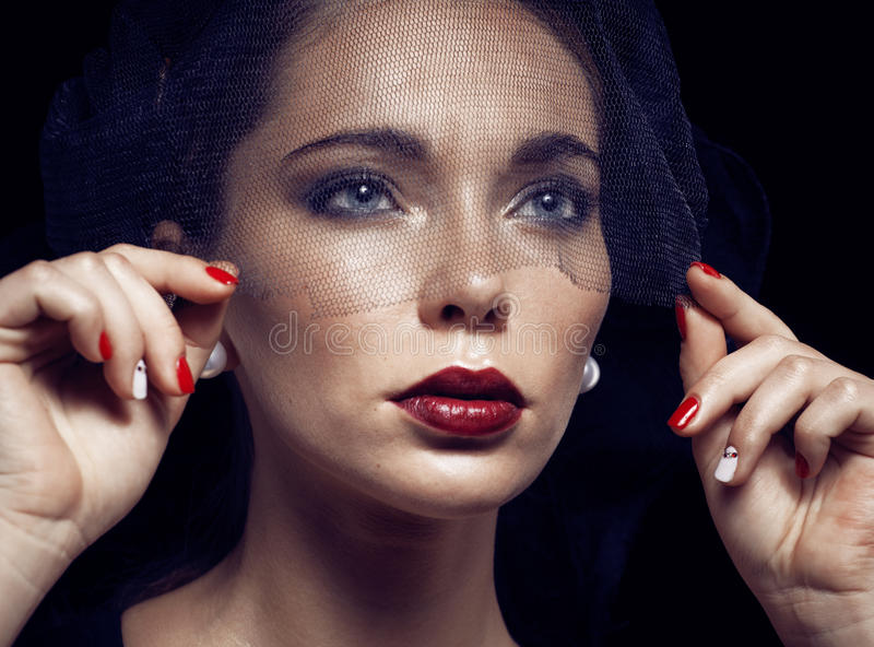 Beauty brunette woman under black veil with red manicure close up, grieving widow, halloween makeup stock photos