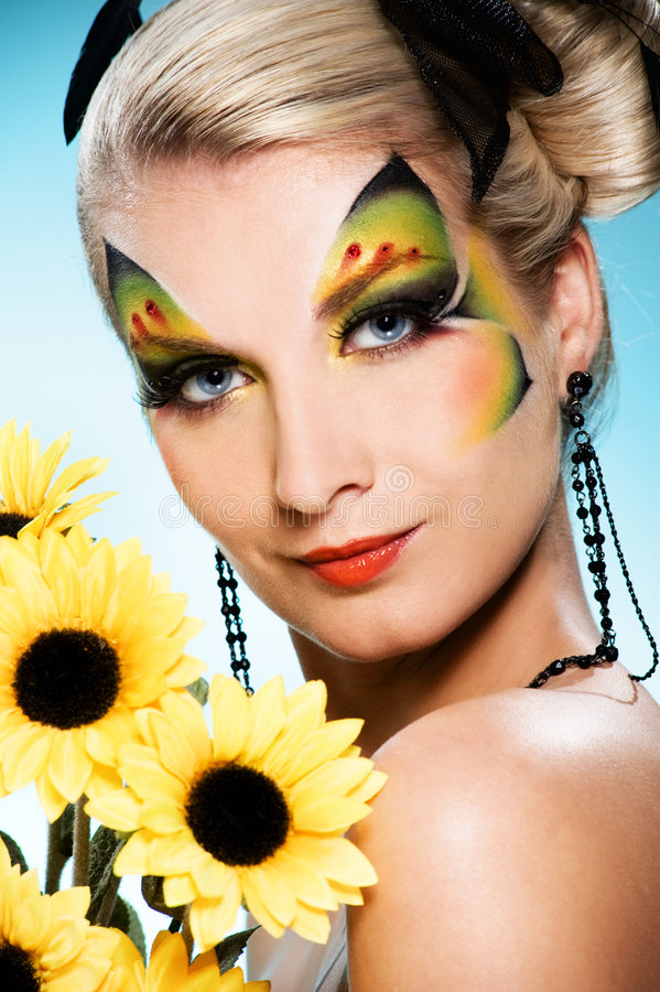 Beauty with butterfly face-art. Young beauty with butterfly face-art and bouquet of sunflowers royalty free stock photos