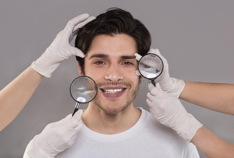 Beauticians examining young handsome man face through magnifiers royalty free stock photos
