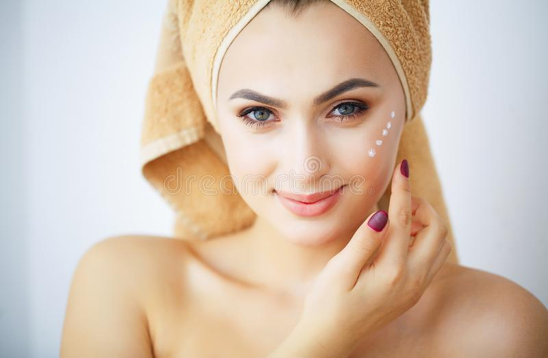 Beauty and Care. Portrait of a Girl with a Brown Towel on the Head. Young Woman With Pure Skin. Holds Cream in Hands. to royalty free stock photography