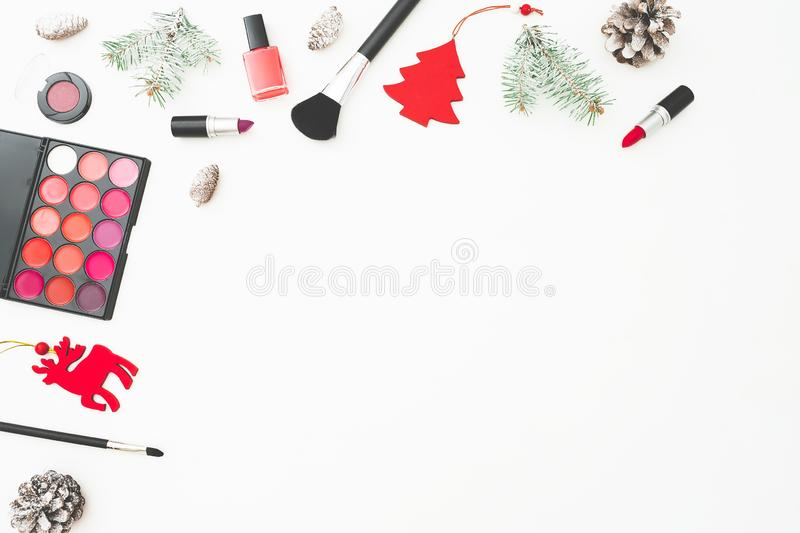 Beauty Christmas desk with cosmetics, accessories, decorations and pine cones on white background. Holiday composition. Flat lay, royalty free stock photos