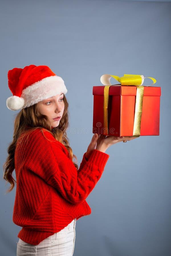Beauty Christmas fashion model girl holding Xmas gift box. Beautiful lady, Long straight flying hair, red santa hat, holding gift stock image