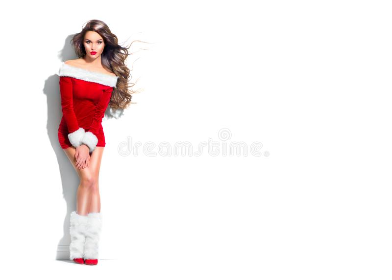 Beauty Christmas fashion model girl, wearing red Santa dress. Sexy brunette young woman with long curly hair. Stylish female fashionable party clothes and royalty free stock image