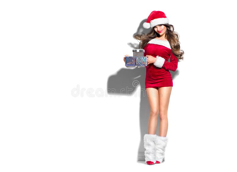 Beauty Christmas fashion model girl with Xmas gift boxes, wearing red Santa Claus dress and hat holding gifts stock photo