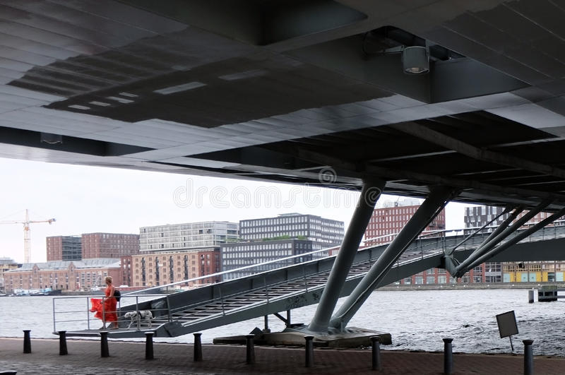 Beauty in the city. Lady in red dress walking her dalmation brings a touch of colour and drama to the undercroft of a bridge in Amsterdam with riverside stock photography