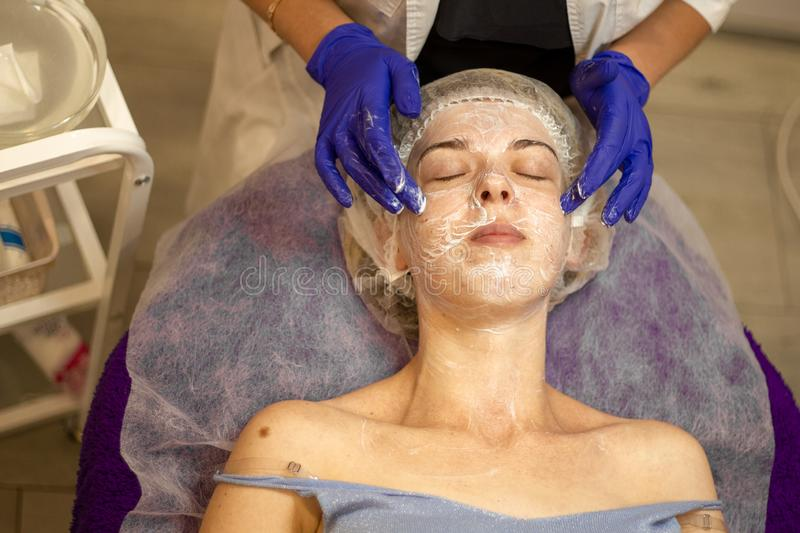 Beauty Clinic.woman gets a professional facial procedure. Beautician makes massage on a woman`s face. face renewal stock image