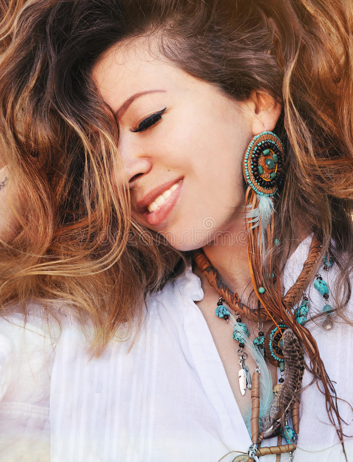 Beauty close up fashion smiling woman portrait with handmade necklace and earrings made with beads, leather and feathers, boho chi stock photos