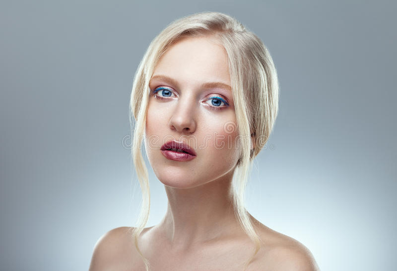 Beauty close up portrait of nordic natural blonde woman. On grey background stock photography