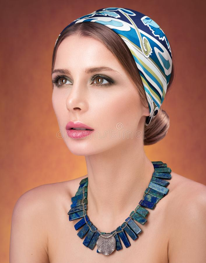 Beauty closeup portrait of beautiful young woman in a headscarf. Necklace on her neck royalty free stock photos