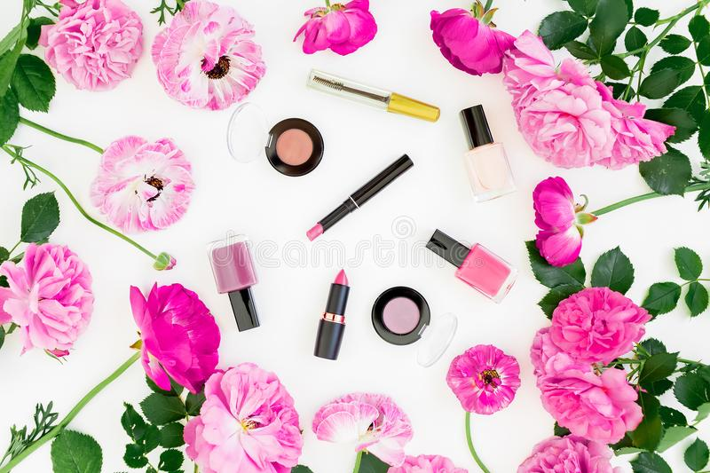 Beauty composition with pink flowers bouquet and make up cosmetics on white background. Top view. Flat lay feminine desk. stock photography
