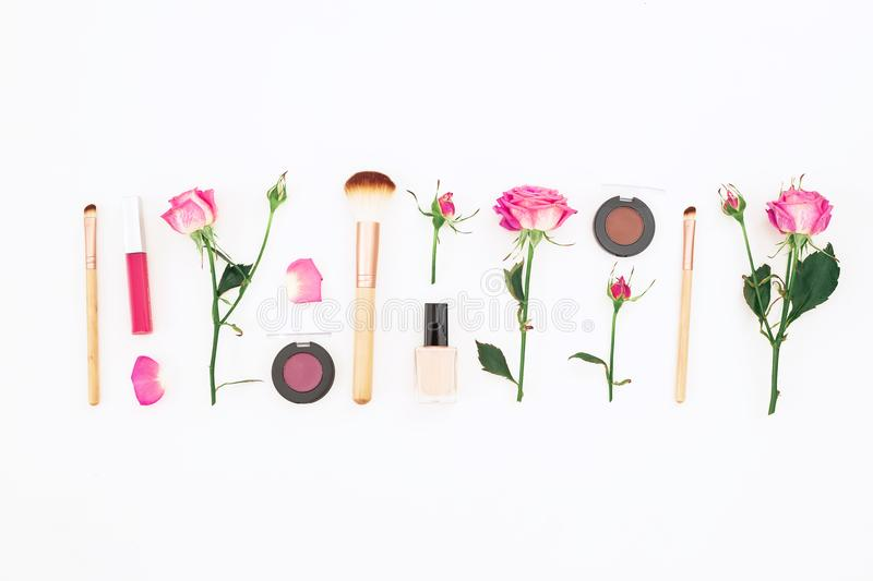 Beauty composition with pink roses and cosmetics on white background. Flat lay, Top view. stock images
