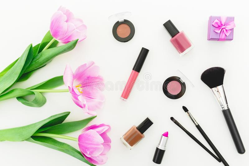 Beauty composition with pink tulips bouquet, cosmetics and gift box on white background. Top view. Flat lay home feminine desk. stock images