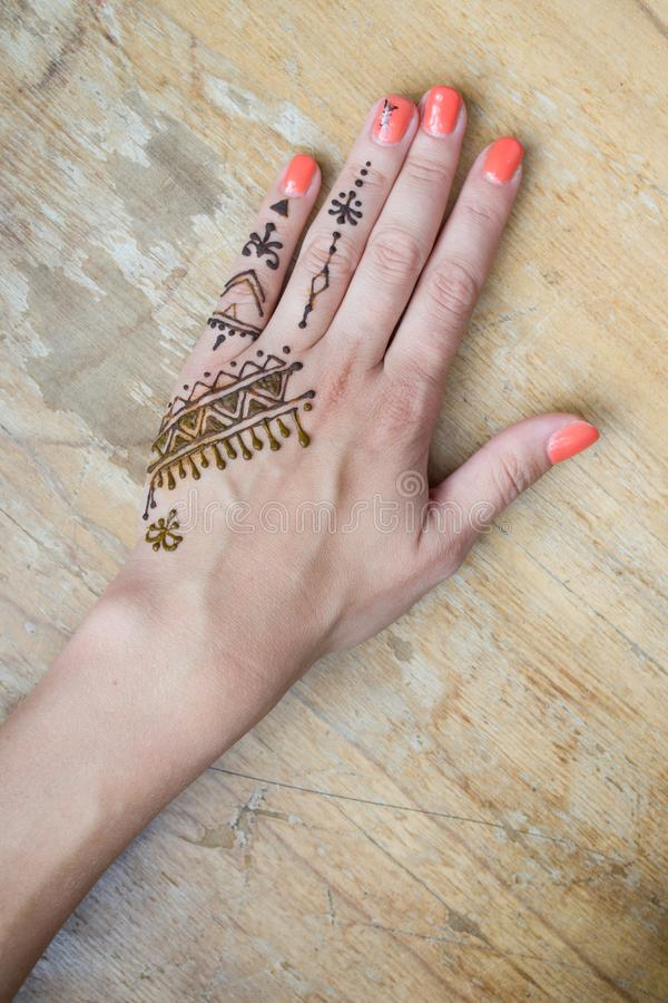 Artist applying henna tattoo on women hands. Mehndi is traditional Indian decorative art. Close-up, overhead view - beauty concept royalty free stock image