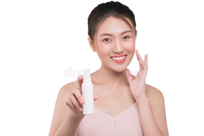Beauty concept. Asian pretty woman with perfect skin holding cosmetic bottle.  stock photo