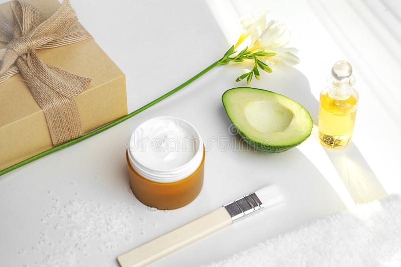Beauty concept avocado, skin care facial essence oil, brush, lily flower and towel on white background. stock images