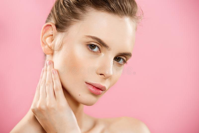 Beauty Concept - Beautiful Woman with Clean Fresh Skin close up on pink studio. Skin care face. Cosmetology. royalty free stock image