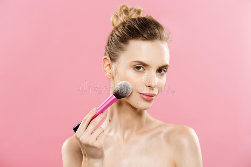 Beauty Concept - Closeup Beautiful caucasian woman applying makeup with Cosmetic Powder Brush. Perfect Skin. on stock photo
