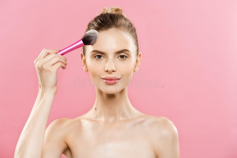 Beauty Concept - Closeup Beautiful caucasian woman applying makeup with Cosmetic Powder Brush. Perfect Skin. on royalty free stock images