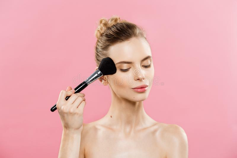 Beauty Concept - Closeup Beautiful caucasian woman applying makeup with Cosmetic Powder Brush. Perfect Skin. Isolated on royalty free stock photography