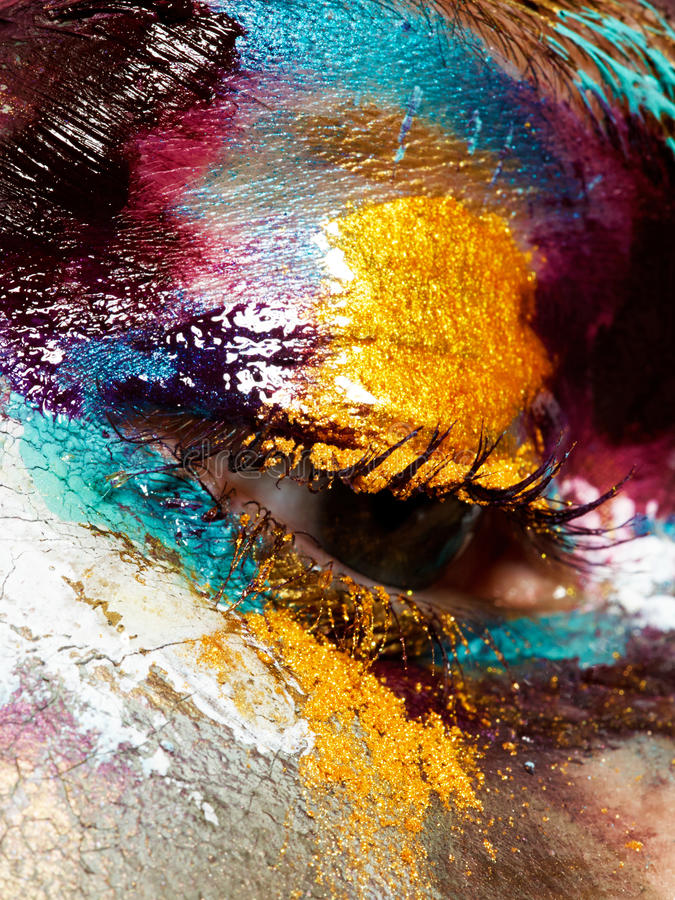 Beauty concept. Perfect artistic, creative makeup. Closeup of beautiful woman`s eye with bright glossy colorful makeup. Makeup with a different texture and stock photo