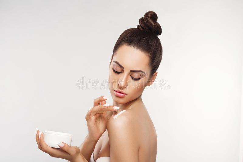 Beauty Concept. Woman Applying  Cosmetics Cream, Spreads it on her shoulder  to moisturize her skin and Smiling. royalty free stock image