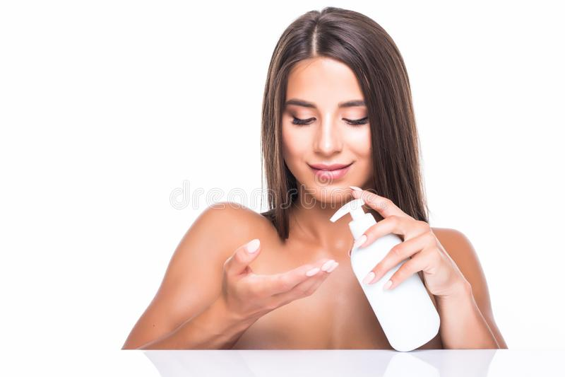 Beauty concept. Beauty woman Face. Closeup of beautiful young woman with fresh skin holding cream bottle in hand applying cosmetic stock photos