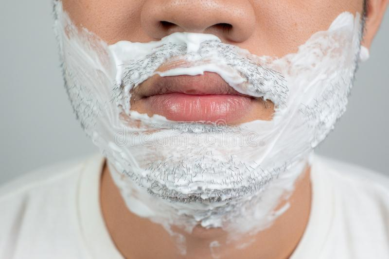 Beauty concepts for health and skin care an Asian guy with a mustache with a beard with a bubble on his face, preparing to shave royalty free stock images
