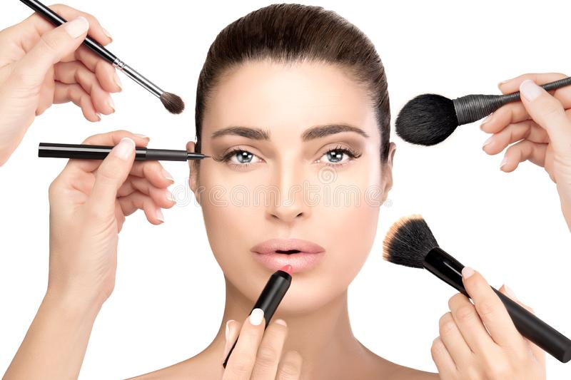 Beauty and cosmetics concept. Beautiful face. Makeup process. Beauty and cosmetics concept with makeup brushes held in the hands of female beauticians royalty free stock photos