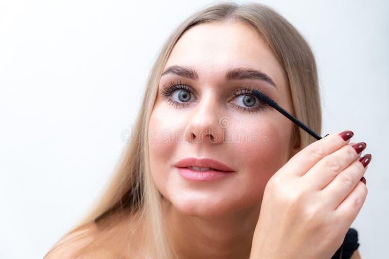 Beauty Cosmetics Sexy vrouw die zwarte mascara op lange, dikke eyelashes met penseel stopt Fashionisch stock foto