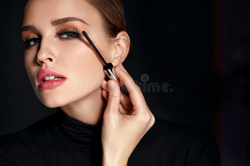 Beauty Cosmetics. Woman Putting Black Mascara On Long Eyelashes. Beauty Cosmetics. Closeup Of Beautiful Woman Putting Black Mascara On Long Thick Eyelashes With royalty free stock photos