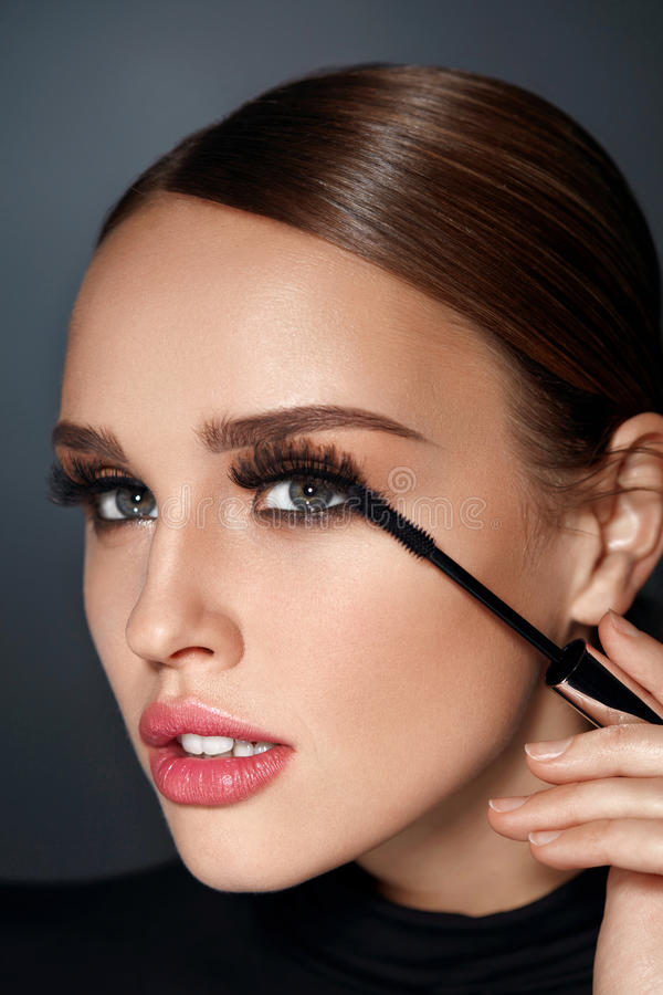 Beauty Cosmetics. Woman Putting Black Mascara On Long Eyelashes. Beauty Cosmetics. Closeup Of Beautiful Woman Putting Black Mascara On Long Thick Eyelashes With stock photography