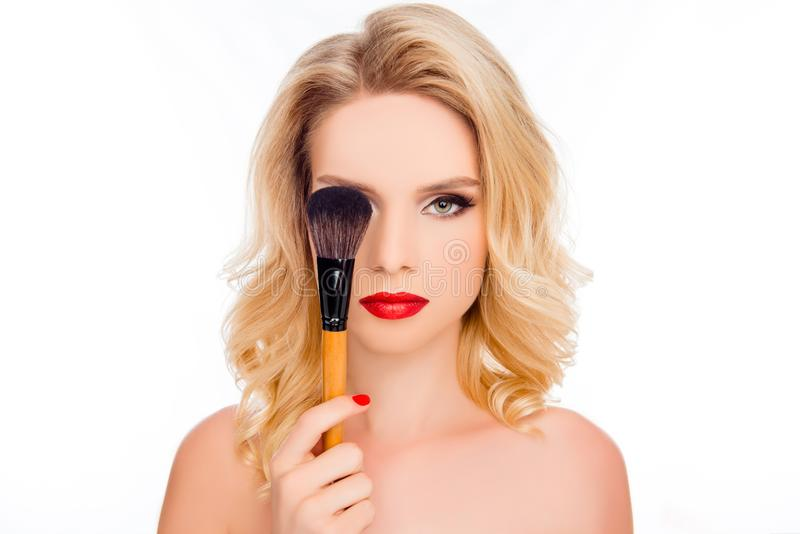 Beauty and cosmetology concept. Close up portrait of pretty blond with bright makeup hiding eye behind make-up brush isolated on stock photography