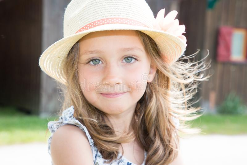 Beauty cute child girl with deep blue eyes in sunny park stock photography