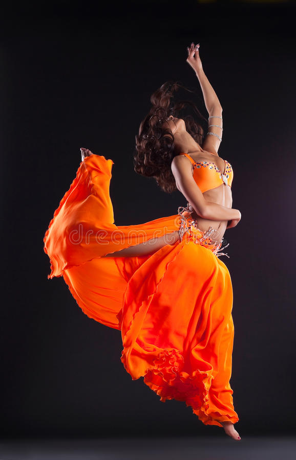 Beauty dancer jump in orange veil - arabian style royalty free stock photo