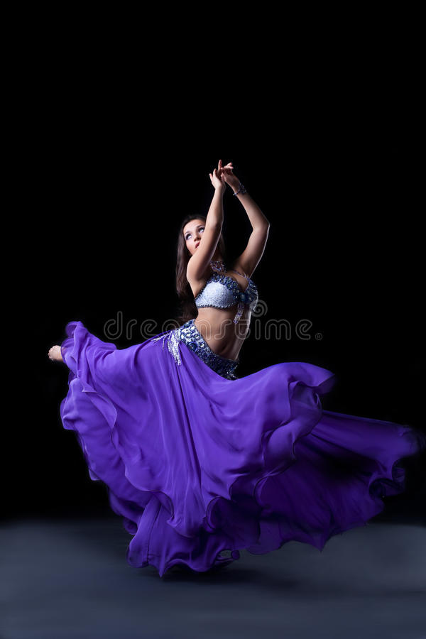 Beauty dancer posing in dark with fly purple veil stock photos
