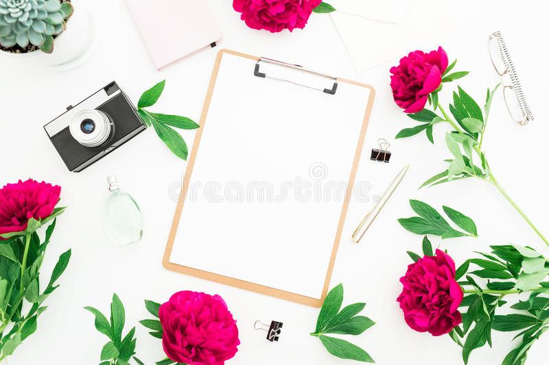 Beauty decorated concept. Blogger or freelancer workspace desk with clipboard, notebook, retro camera, peonies and pen on white ba stock illustration