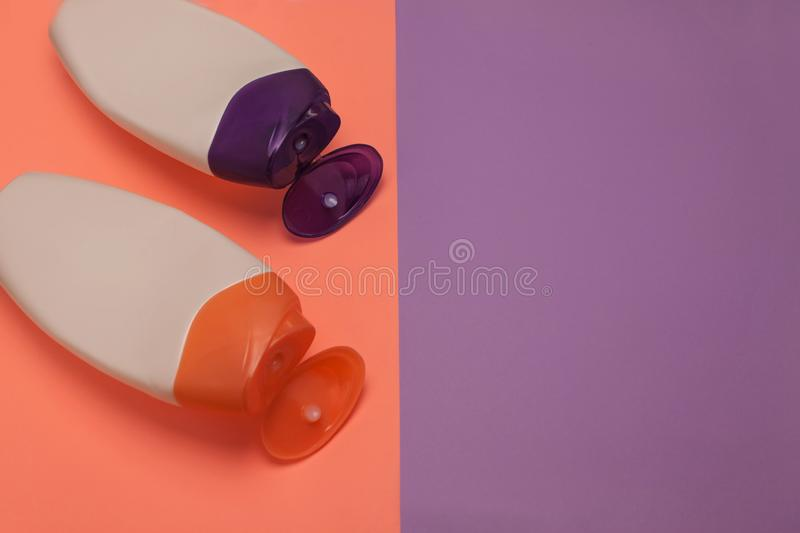 Beauty, decorative cosmetics bottles. Peach and purple colors background, flat lay, top view, minimalistic pop-art style stock image