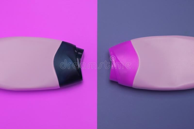 Beauty, decorative cosmetics bottles. Pink and purple colors background, flat lay, top view, minimalistic pop-art style stock photos