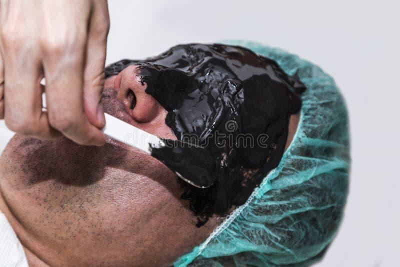 Beauty doctor apply skin alginate seaweed black mask to male patient face. Beauty doctor apply skin care moisturizing alginate seaweed cleansing dry black mask royalty free stock photo
