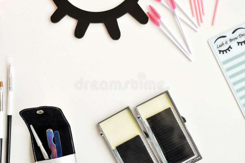 Beauty of eyelashes and eyebrows: eyelash extension tools and decor on white background with copy space. top view. Flatley. Beauty of eyelashes and eyebrows royalty free stock photography
