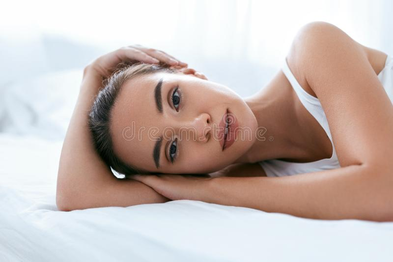 Beauty Face. Beautiful Woman With Healthy Skin On White Bed royalty free stock photos