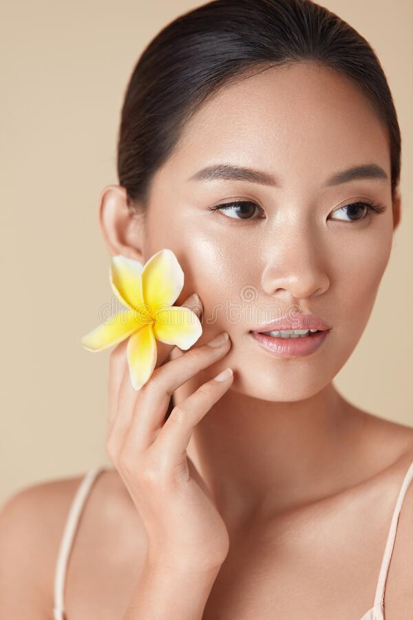 Free Beauty Face. Flower And Model Close Up Portrait. Beautiful Asian Woman With Plumeria Looking Away Against Beige Background. Royalty Free Stock Photo - 187832535