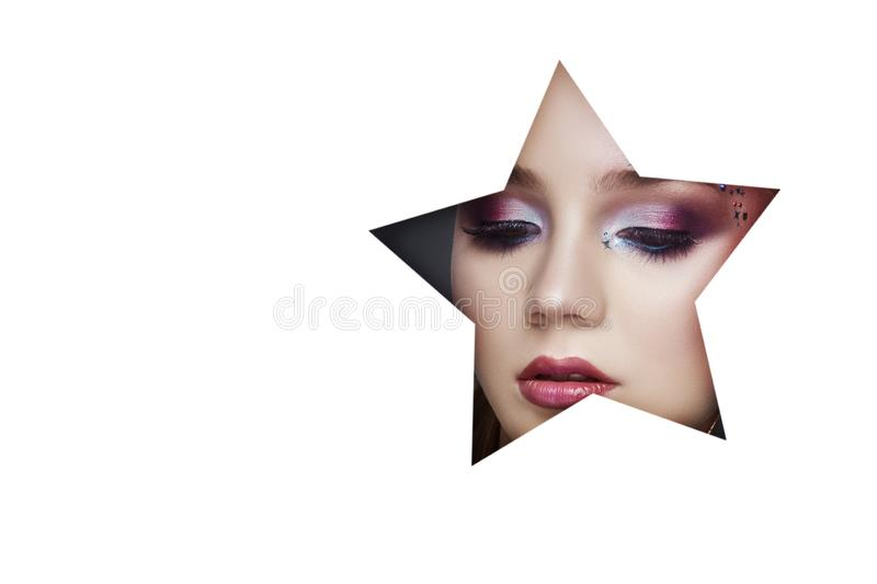 Beauty face makeup of a young girl in a white paper hole. Woman with beautiful makeup, bright eyes, luminous shadow in star hole. stock photography