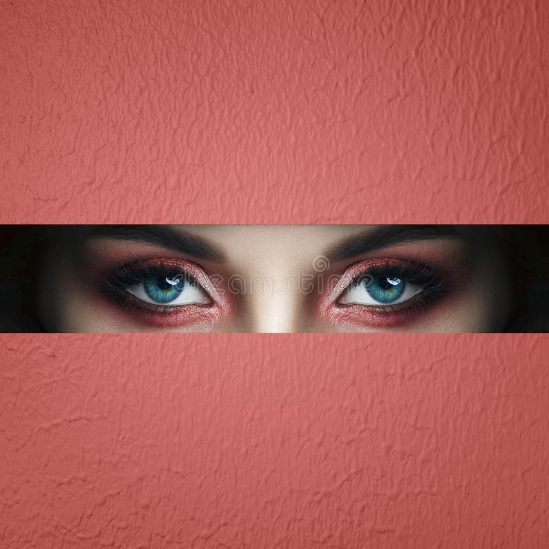 Beauty face red makeup eyes of a young girl in a slit hole of pink red paper. Woman with beautiful makeup red glowing shadow, big stock photography