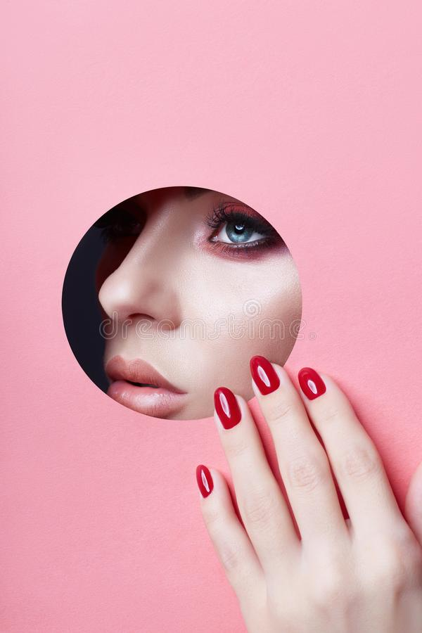 Beauty face red makeup plump lips red nails of a young girl in a round slit hole of pink paper. Woman with beautiful makeup plump royalty free stock images